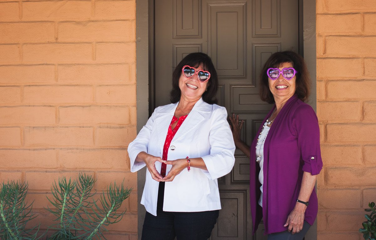Lynn Alcala and Victoria Alcala-Kelley pose in front of their childhood home turned historical building in Costa Mesa