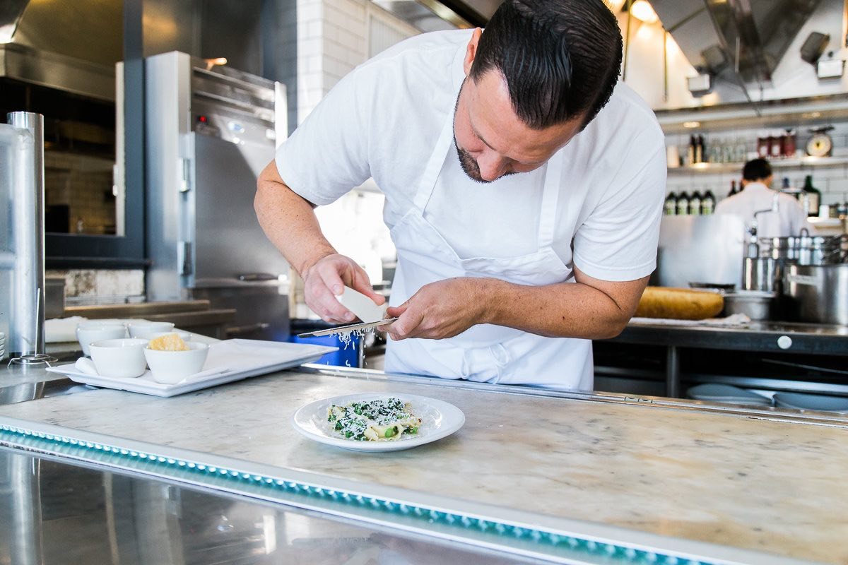 Pizzeria Ortica Executive Chef, Justin Miller, Finishes a Plate with Freshly-Grated Ricotta Salata.
