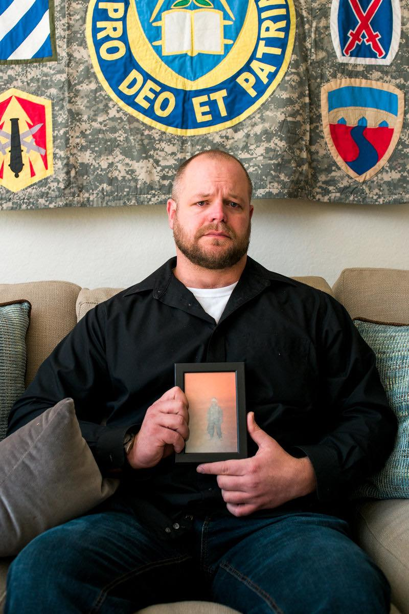 Combat Veteran Aaron Steckman Holds A Photo Of His Fallen Friend