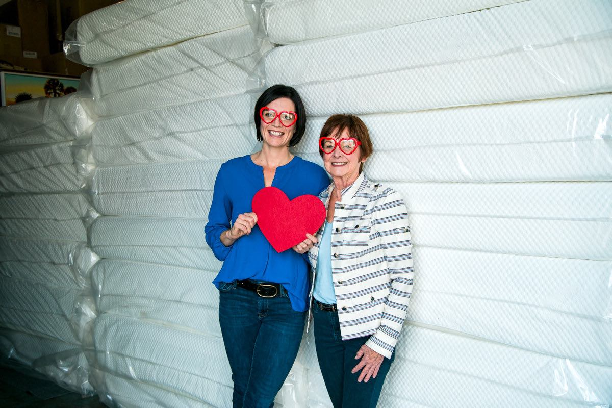 Robyn Phillips and her mother, Beth, pose with stacks of donated mattresses at the Furnishing Hope warehouse