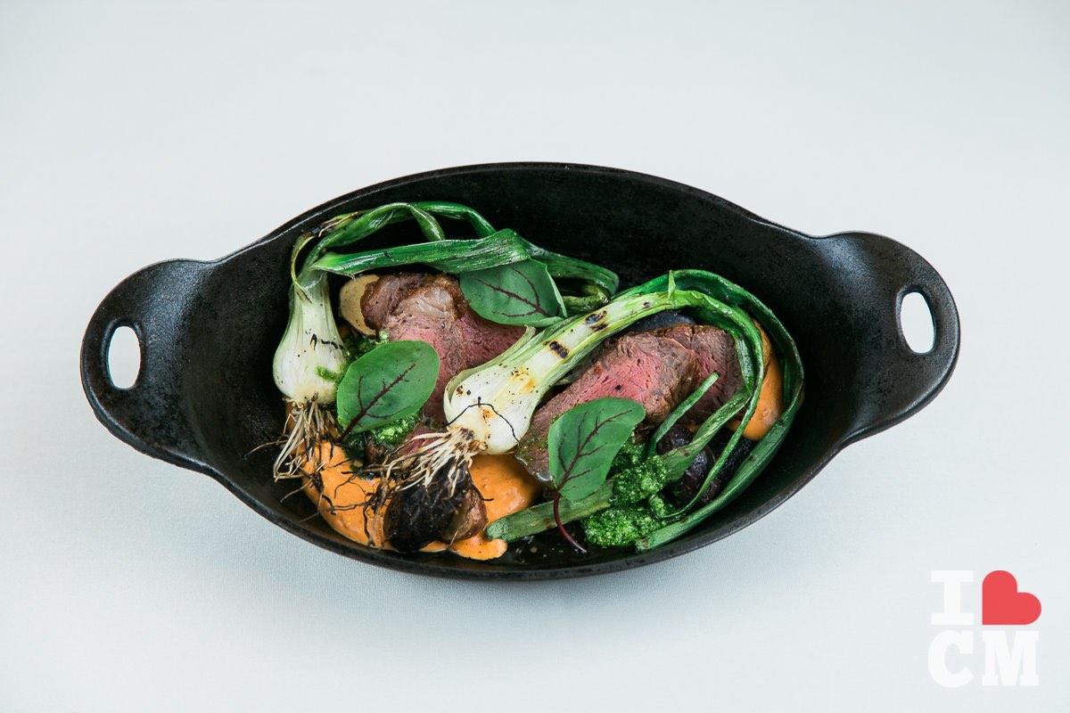 Beautiful Presentation of Prime New York Steak with Roasted Green Garlic Bulbs and Feta Salsa Verde by Mesa Verde Country Club's Executive Chef, Chris Chun