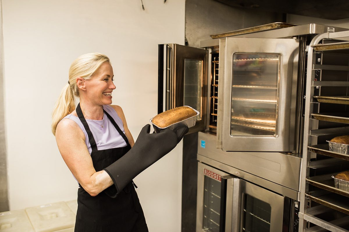 I Heart Costa Mesa: Baker, Christine Bren, pulls a fresh-baked loaf of gluten-free bread out of the oven to cool. At Lavender Lane Baking Co. in Costa Mesa, Orange County, California. (photo: Brandy Young)